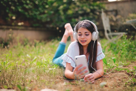 woman-lying-down-on-ground With Headphone
