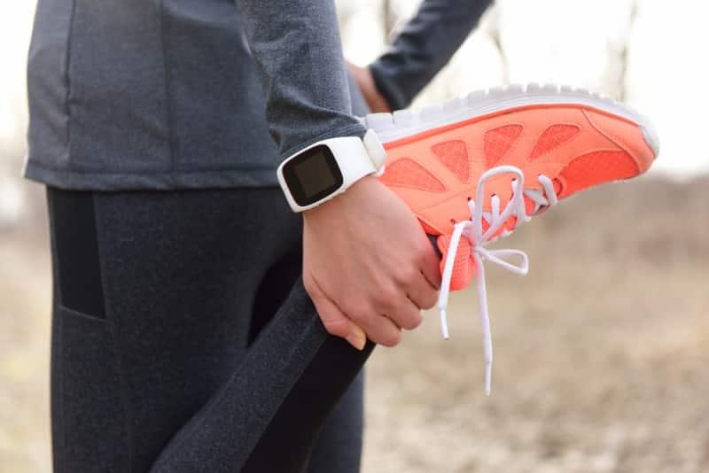 stretching women wearing fitness tracker